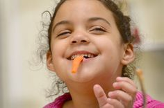The littlest Vegans...Feeding children a vegan diet is growing in popularity...Maya Parker-Rollins, 5 munches on carrot sticks at the Parker-Rollins home.