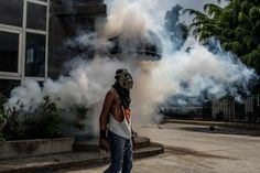 An anti-government protester stands near a teargas cloud during clashes against Venezuela's security forces in Caracas. (Alejandro Cegarra/For The Washington Post)