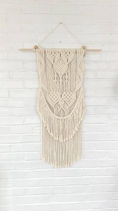 "70s Macrame is back with a modern twist This gorgeous macrame wall hanging is made with cotton rope The wall hanging is attached to a square Wood dowel It measures 24"" wide and 37"" long. The length measurement is from the dowel to bottom of fringe and the width is from one end of"