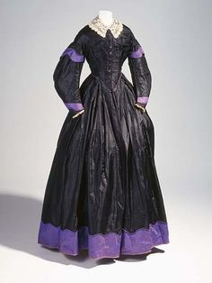 "Half-mourning dress, 1855-65 (ca 1860-63?), the North Carolina Museum of History  "" TWO-PIECE HAND-SEWN, BLACK SILK DRESS, FITTED, LINED, BONED BODICE, PLAIN ROUND NECKLINE, EIGHT PURPLE/BLACK SQUARE DECORATIVE BUTTONS ABOVE HOOK AND EYE CLOSURE AT..."