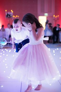 Light up dance floor and bubble wand with flower girl twirling in a tulle skirt at wedding reception