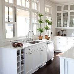 All white kitchen with transom windows over a large stainless steel sink with gooseneck faucet accentuated by crisp white counters over shaker style cabinetry with built-in wine cubbies to the left and stainless steel dishwasher to the right. Backsplash For White Cabinets, White Countertops, White Kitchen Cabinets, Kitchen White, Wall Cabinets, Shaker Cabinets, Shaker Kitchen, Upper Cabinets, Kitchen Backsplash
