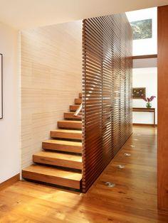 Escalera oculta tras una elegante celosía de madera.