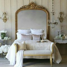 Bed with oversized gilt mirror as headboard.