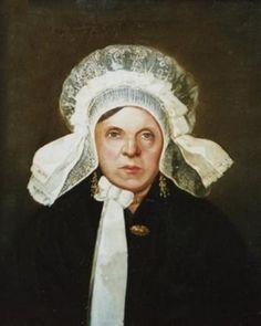 De dame op deze foto is Maria Catharina van Roij-Sanders (*Helmond, 1804/+Veghel, 1863). Ze was gehuwd met de Veghelse koopman Hendrik van Roij. Je kunt zien dat mevrouw Van Roij een aanzienlijke vrouw was. Ze draagt een witte kanten muts met een strik onder de kin. Ook draagt ze grote gouden oorhangers, een halsketting en een broche. Dit was de mode bij rijke Veghelse dames rond 1860.