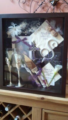 This is a shadow box I created from my wedding keepsakes.  I put our champagne flutes, cake servers, my garter, the comb I wore in my hair, an invitation, the cake topper, napkins, bird seed pouches, etc. in it.  I just didn't want to box this stuff up, so now I can see everyday!!!