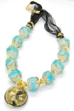 Captivating Murano glass necklace. Made in Venice, Italy, precious, bright, imaginative, customizable. Beads in turquoise and white tonality with relief decoration in bronze and gold dust. Wholesale Italian jewelry. Black organza ribbon. Glamorous the round pendant with 24 karat gold leaf fused into the crystal glass.