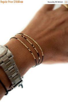 Eine lustige und zarte solid gold Discokugel Freundschaft Armband gemacht mit 20 facettiert Runde 14k gelbe Goldene Perlen sorgfältig aufgereiht auf Seidenkordel und abgeschlossen mit einer verstellbaren Korn in der Rückseite und zwei niedlichen Troddeln an den Enden. Die Perlen können bewegen, so ist es völlig Ihnen überlassen wie Sie die Armbänder - mit alle Perlen in eine schöne Zeile oder Verbreitung rund um die Seidenkordel tragen. Das Armband kommt montiert auf einer Geschenkkarte…