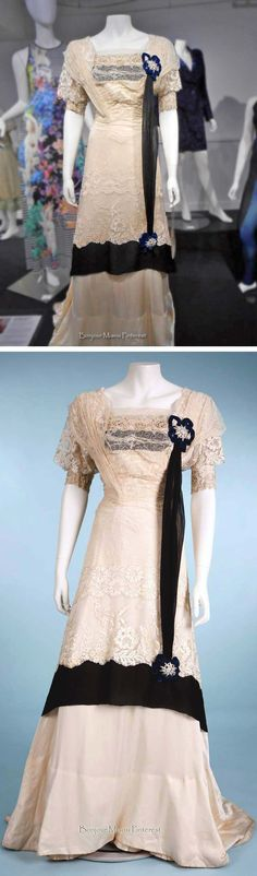 Evening dress ca. 1912. Off-white Alençon lace and silk satin with black silk crepe trim, peacock blue velvet trim around rosette décor on bodice and skirt. Stephens College Costume Museum Facebook and Pinterest