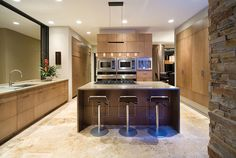 Soft maple cabinetry lies flush with the walls while Dacor double microwaves make a catered affair a snap. No place in this kitchen is without perfect lighting, especially over the granite counter with its adjustable six-torch lighting bar from Lightstyle. Photo by Harvey Smith Photography.