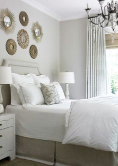 White and beige #bedroom with #sunburst #mirrors.