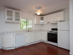 BEFORE: While the buyers liked the open space, the laminate floor, tile countertops and awkwardly-spaced cabinets were all in line to be replaced.
