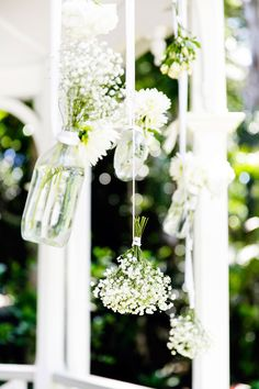 hanging vintage bottles and bunches of flowers for a ceremony backdrop | Photography by callibphotography.com.au