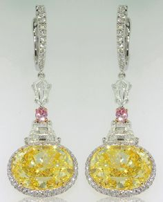 Two perfectly matched vivid yellow oval diamonds are the center stones of these…