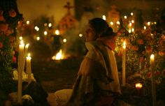 A woman sits next to a gravesite during Day of the Dead celebrations at the cemetery in Arocutin, Mexico, early Monday, Nov. 2. According to tradition, candles are lit to guide wandering souls back to their families during Day of the Dead.