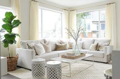 Gorgeous living room features an off white sectional lined with pale pink velvet pillows as well as yellow and gray ikat pillows in Bansuri Fabric paired with a white marble top box frame coffee table and white trellis stools atop a cream diamond pattern rug.