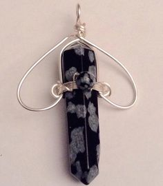 This Snowflake Obsidian pendant is almost 2 inches long x 1 inch wide. Comes with satin cord.