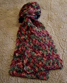 The Kaleidoscope Scarf stitch pattern gives the illusion that the scarf is composed of braided strands of color. In reality, the self-striping sock yarn and the off-set shells contribute to this...