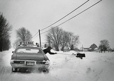 Although not required to deliver to boxes blocked by snow – customers are supposed to dig mailboxes out – this rural carrier is seen using an extension pole and hanging half out of his car to deliver the mail in Cleveland, Ohio, 1975.