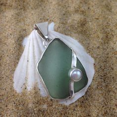 Sterling silver setting showcasing light green sea glass with sterling and fresh water pearl overlay. Measures 2 inches long and a little over an inch wide. Can be worn on a strand of fresh water pear