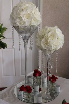 Centros de mesa con copas gigantes, guirnaldas de cristal y espejo como base.
