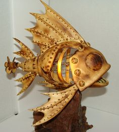 Mechanical fish with propeller that turns by hand. Carving has chain inner parts and saw blade teeth.