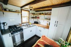 BEST KITCHEN  This is the Chimera tiny house on wheels by Wind River Tiny Homes. From the outside, you'll see a flat roof with plenty of windows, grey siding, and a bright red door. When you go inside you&…