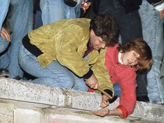 Two young Berliners chisel souvenir pieces of concrete from the Berlin Wall at the Brandenburg Gate on Nov. 11, 1989.