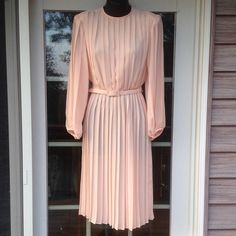 2.99ship one hour Vintage pink/peach pleated dress Beautiful dress. Sheer. Belt around waist. Buttons o back and at the end of sleeves. Padded shoulders. The dress is in absolute great condition. There are a couple of blemishes as seen in pictures that are nearly invisible on dress. Made in USA. Trades Monica Richards Dresses Long Sleeve