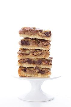a stack of low carb pecan pie bars with chocolate sitting on a white cupcake stand