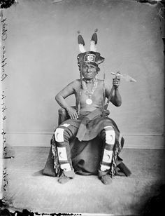 Portrait of Tcha-Wan-Na-Ga-He (Buffalo Chief) - Oto, in Native Dress wearing fur and feather headdress and peace medal, holding pipe-tomahawk, undated by William Henry Jackson (1843-1942)