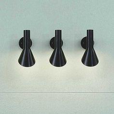 Arne Jacobsen designed the AJ wall lamps fro the SAS Royal Hotel in Copenhagen. Produced by louis Poulsen