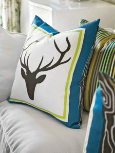 "Woodsy meets welcoming in the cushy ""Stag Head"" throw pillow backed in ""Faux Bois"" fabric, both designed by Tobi Fairley for her home collection."