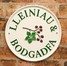Round Cream sign with racing green letters and bramble motif. www.rockartisansigns.co.uk