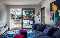 Mesmo em meio a outras cores da iluminada sala de estar, o sofá predomina e faz parceria com o pufe roxo no projeto do escritório Reinach Mendonça