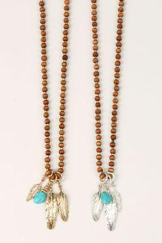 Metallic Feather + Turquoise Stone Necklace Metallic feather pendants & turquoise stone on long, wooden bead necklace. Chose from Silver or Gold. Necklace measures approx 30″