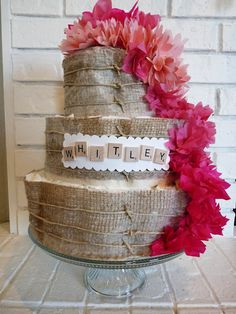 sweet, modern/vintage diaper cake I made for @Kelli Warren... Made with burlap paper, tissue flowers and Scrabble pieces.