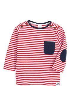 Camisola de mangas compridas: Camisola de mangas compridas em jersey macio de algodão com botões nos ombros. Tem bolso no…