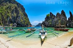 Paradise shore - Banca boats float peacefully at shore in front of an incredible view of the limestone cliffs that make up the Bacuit Archipelago. - Taken near El Nido, Palawan, Philippines.