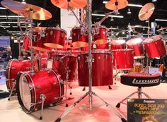 Ludwig drumkit in Red, with circle of crashes and toms. Seen at the Namm show in 2015.  DRUMS & DRUMMING JOY  - https://www.pinterest.com/DianaDeeOsborne/drums-drumming-joy/ - RESEARCH DdO:) -  NAMM show is the place to hunt out all of the latest drumming gizmos, gadgets and innovations for drummers. chock-full of artist kits, signature cymbals and special gear. This is a LUDWIG drumkit, according to stool's company logo. Photo pinned via  Michael LoBue.