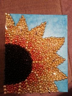 A DIY sunflower canvas made with paint and plastic Mardi Gras beads!