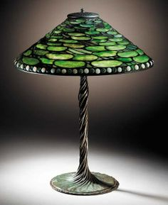 A 'LILY PAD' LEADED GLASS AND BRONZE TABLE LAMP Tiffany Studios, circa 1910 25陆in. (64.3cm.) high, 20in. (50.3cm.) diameter of the shade, with finial the shade tag stamped TIFFANY STUDIOS NEW YORK 1502-20, the twisted vine base stamped TIFFANY STUDIOS NEW YORK 443