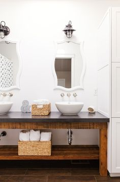 White bathroom with freestanding sinks and matching mirrors