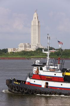 Tugboat crossing by the, Louisiana State Capitol building, Baton Rouge, Louisiana.