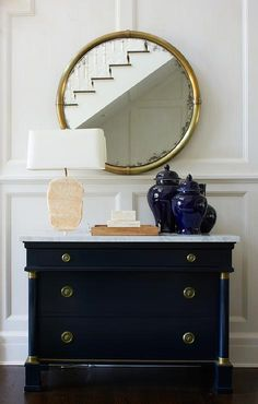 Classic blue and white foyer clad is full wainscoted walls holding a round gold mirror over a navy blue chest adoring gold knobs and topped with navy blue ginger jars. Foyer Decorating, Interior Decorating, Interior Design, Decorating Ideas, Interior Styling, Decor Ideas, Cafe Interior, Interior Exterior, Living Room Sets