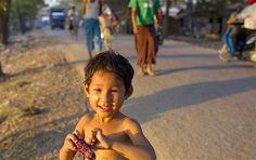Image: A child eating (© Gemunu Amarasinghe/AP)A child eats boiled corn on the roadside of an improvised neighborhood in suburban Yangon, Myanmar.