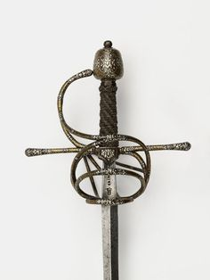 Swept hilt rapier, c. 1600. Steel hilt, damascened in gold and encrusted with chiselled silver. The blade is stamped with spurious marks 'CAINO' (Milanese bladesmith) and 'TO' in a shield surmounted by a crown (Toledo mark). Victoria and Albert Museum