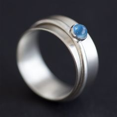 Sterling silver spinner ring with a 4mm blue topaz cabochon. Handmade by Rebecca Cordingley.