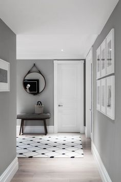 Moody grey walls with white trims and door: this creates the perfect background for a gallery wall. Combined with light wood floors and a strong graphic carpet, this is a sophisticated hallway. http://homeology-academy.teachable.com/ www.homeology.co.za