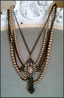 old pearls with rhinestones and metal medal on a schmancied up cross